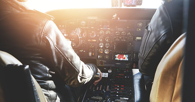 Aerospace transport and people. Two pilots dressed in uniform flying jet airliner on sunny day sitting inside aircraft cockpit surrounded by equipment. Selective focus on captain's hand on power lever