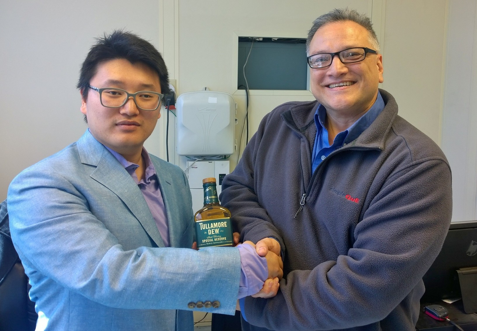 "Pictured is Jay Wang, operations director with Jim Lee, simpleQuE president and a 12 year bottle of ""victory"" scotch to celebrate!"