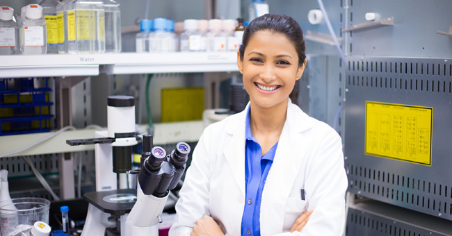 Closeup portrait young smiling scientist in white lab coat standing by microscope. Isolated lab background. Research and development.