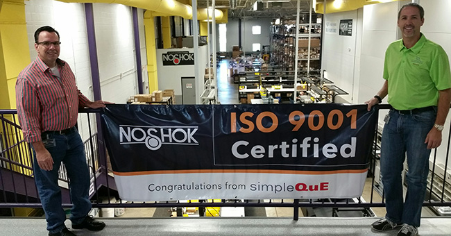Barry Rowley, Quality Assurance Manager (LEFT) and Christian Cole, Vice President (RIGHT) proudly display NOSHOK's ISO 9001:2008 banner at the factory in Berea, Ohio.    Photo courtesy of: Jennifer Briese, simpleQuE Lead Consultant who worked with Chris and the entire NOSHOK team for 3 months to prepare for the certification.